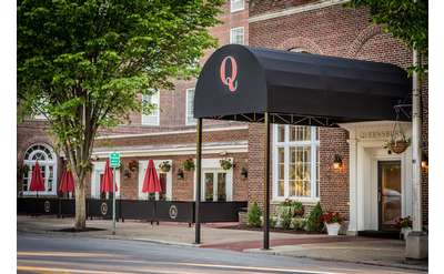 black awning with a red Q on it in front of an entrance to the queensbury hotel