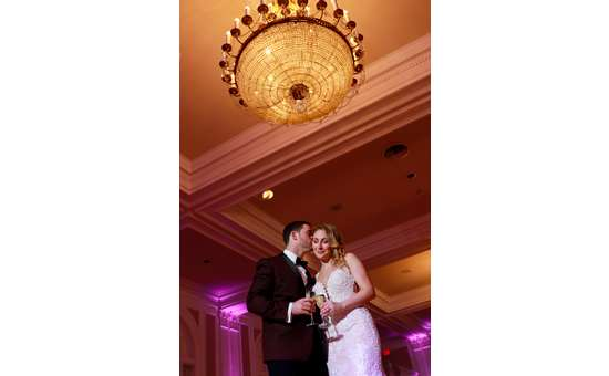 couple kissing on cheek under chandelier