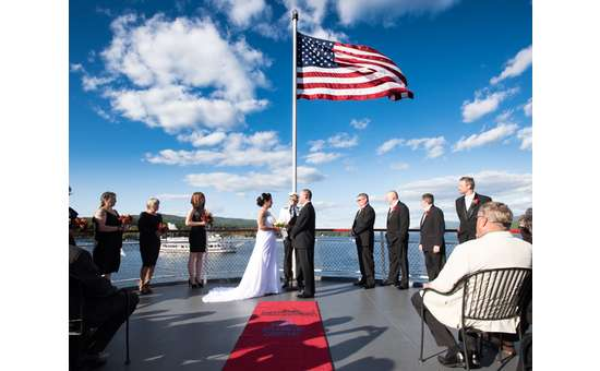 bride and groom getting married on the bow of a boat under a large american flag
