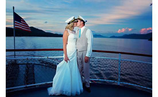 bride and groom wearing captain's hats and kissing on a large steamboat at sunset
