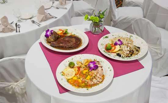 beautiful plated food on a small round table with a white and pink tablecloth