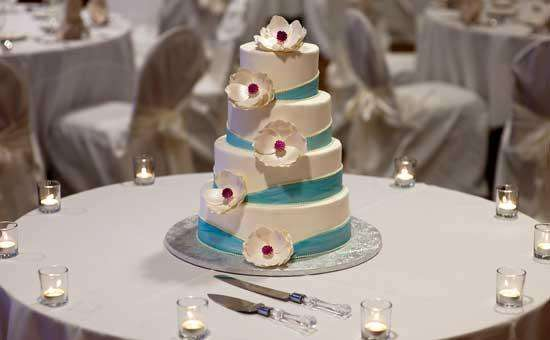 a four-tiered wedding cake, ivory with a teal stripe running up through it, surrounded by small candles
