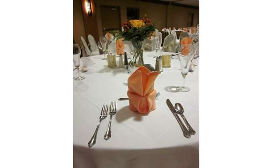 close up of a table setting at a wedding with a peach napkin folded where the plate would be and matching peach-colored flowers as a centerpiece