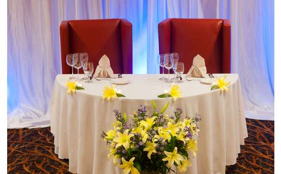 the couple's small, special table with white linens, glassware, and four yellow flowers as decorations with a larger bouquet of yellow flowers in front of the table