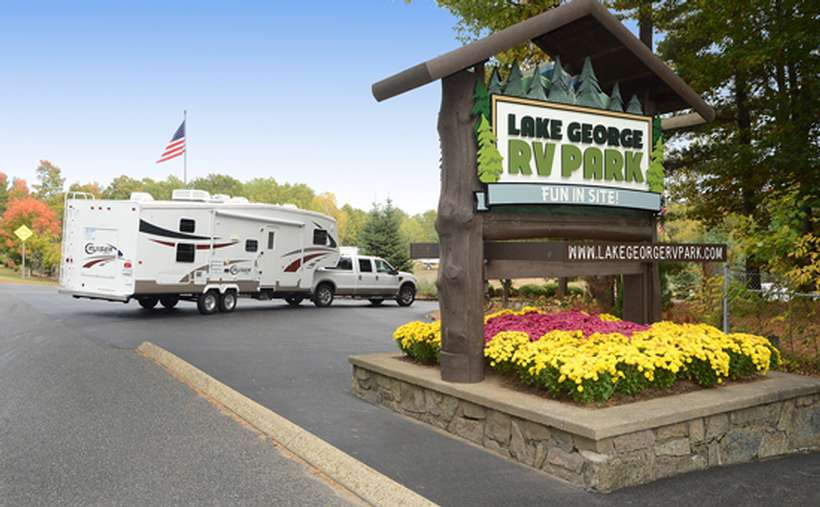 the sign for lake george rv park with a rv in the back