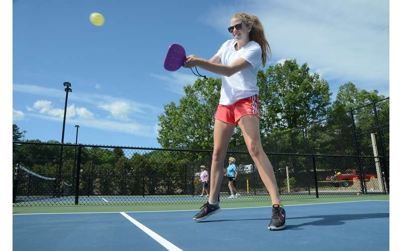 a woman playing pickleball on a court