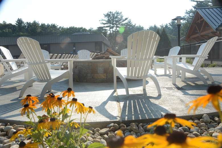 white adirondack chairs in a circle around a fire pit