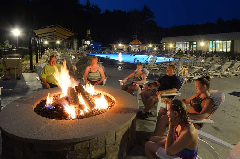 people in white adirondack chairs sitting around a firepit at night