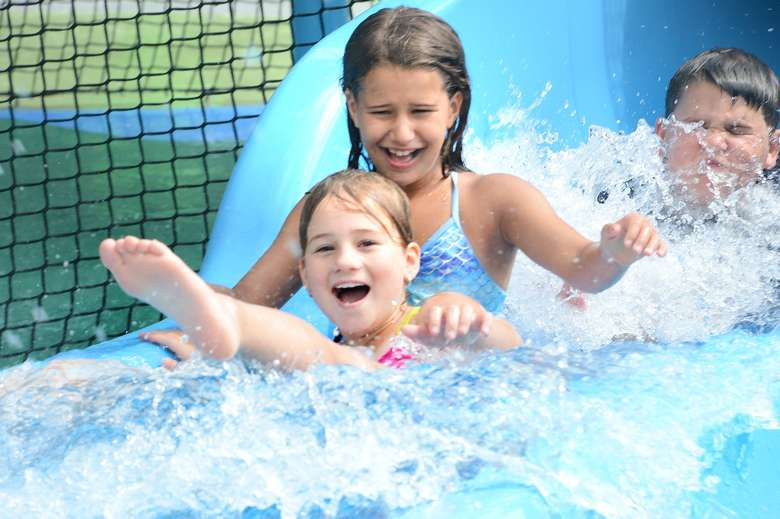 three kids at the bottom of a waterslide