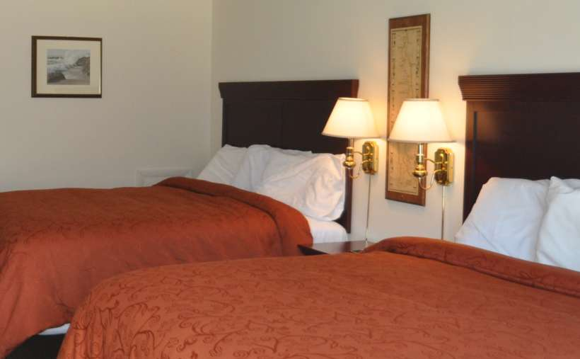 two beds with orangeish red bedspreads