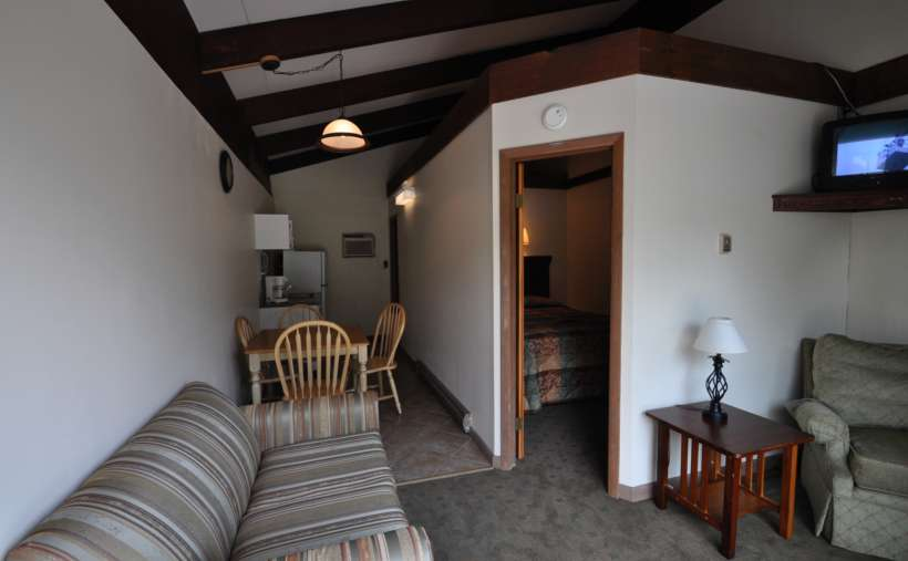 a living room area with striped couch, dining area, bedroom visible, TV
