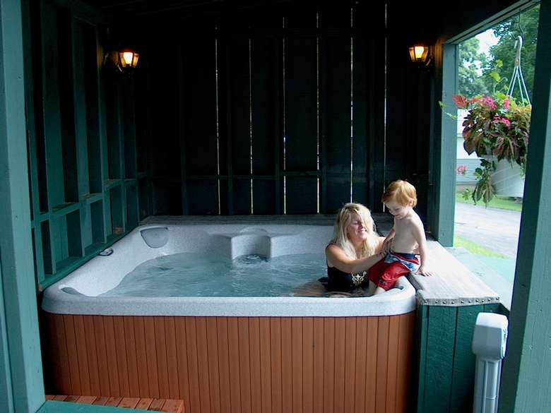 woman in hot tub easing her little boy in