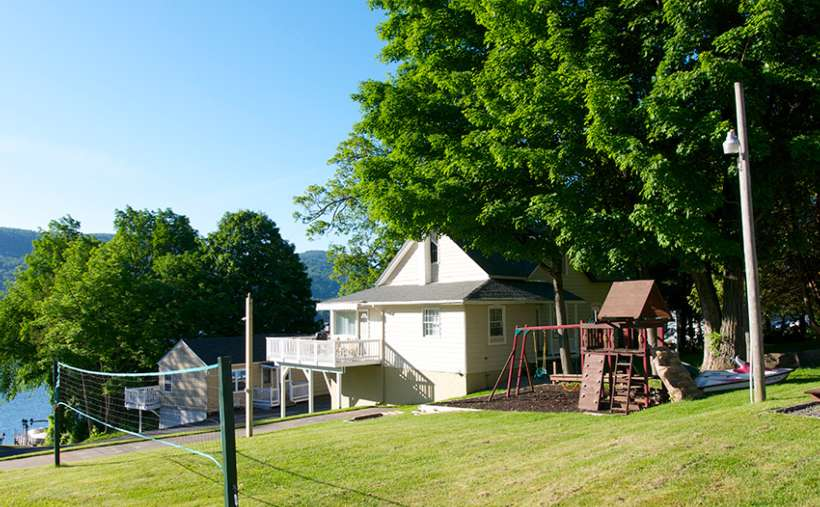 a house with a playground and a volleyball net