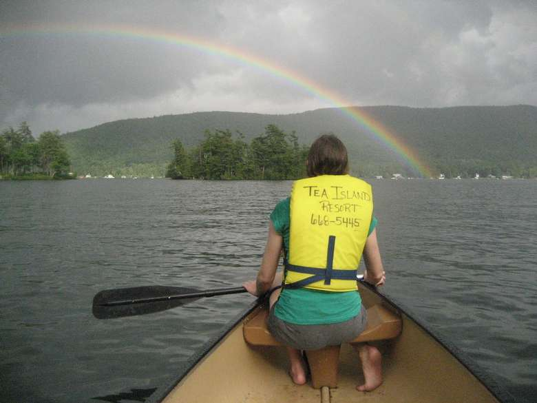 person on rowboat looking at a rainbow