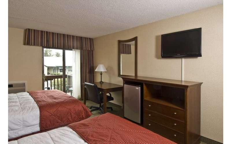 a guestroom with two beds that have red blankets with a tv on the wall in front