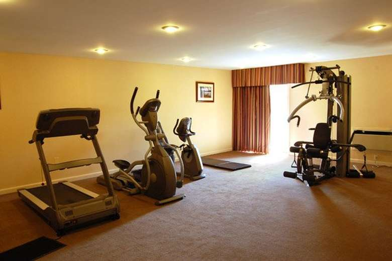 a fitness center with a treadmill and other equipment
