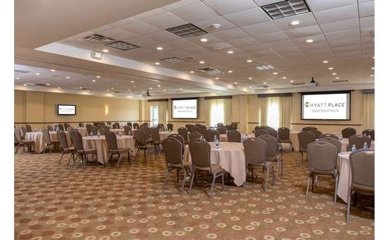 large room set up in a banquet style with individual round tables set with linens