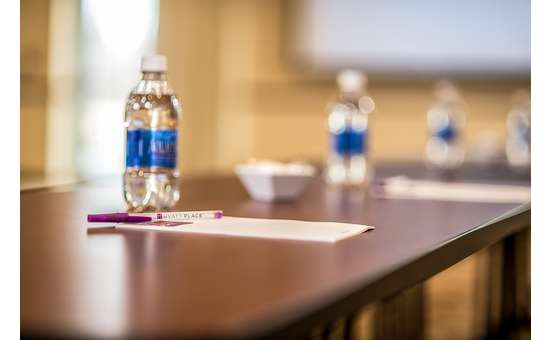 closeup view of a table set with bottled waters, notepads and pens with white panel in background