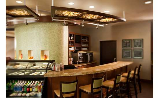 wood bar with several stools in front and a variety of fruit drinks, coffee dispensers, wines and other alcoholic beverages