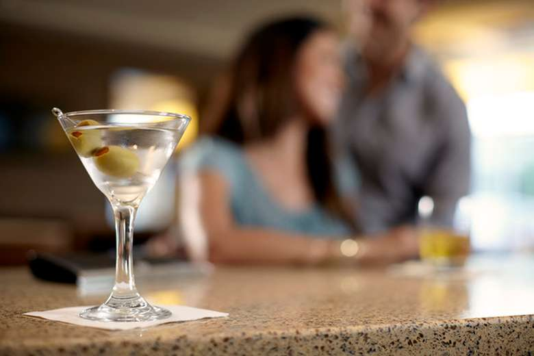 martini with olives in a martini glass set on a bar with blurry image of couple in the background