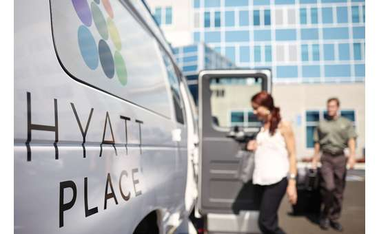 guests getting on hotel shuttle with hyatt place displayed on side