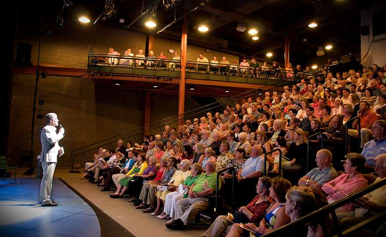 man speaking to a theater audience