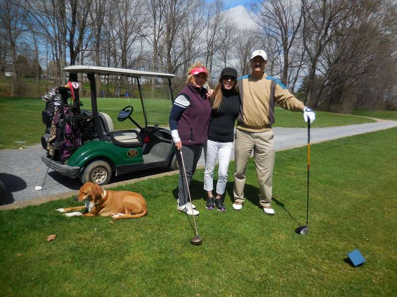 three golfers and their dog posing in front of a golf cart