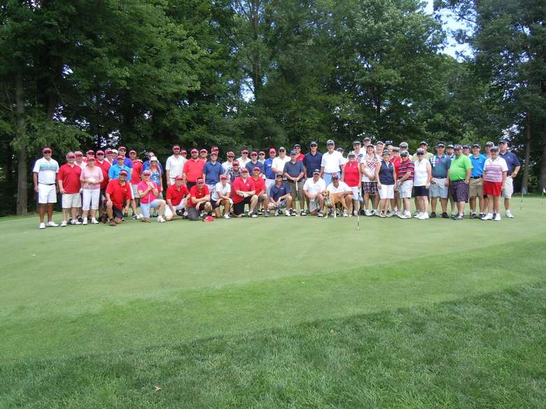 large group of golfers posing before a tournament