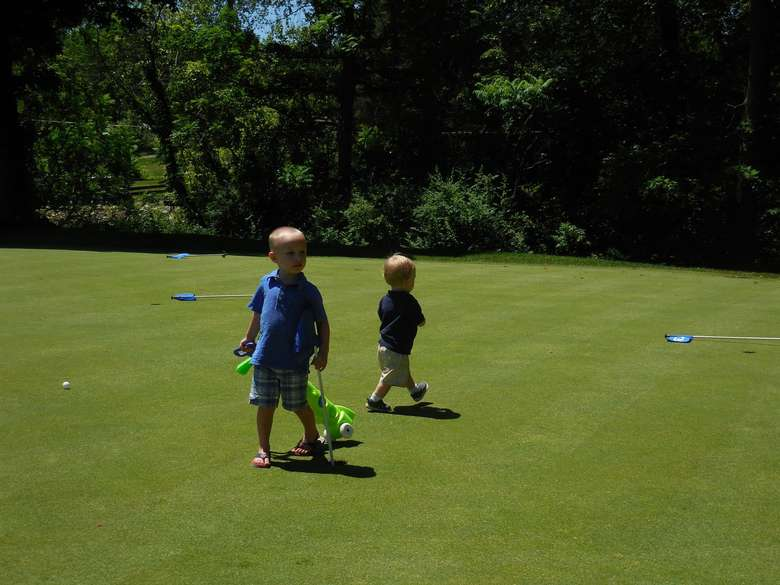 two young boys walking on a golf course