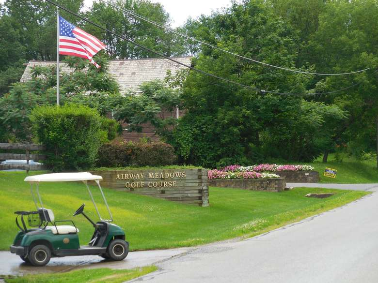 front entrance of airway meadows with a golf cart and an american flag