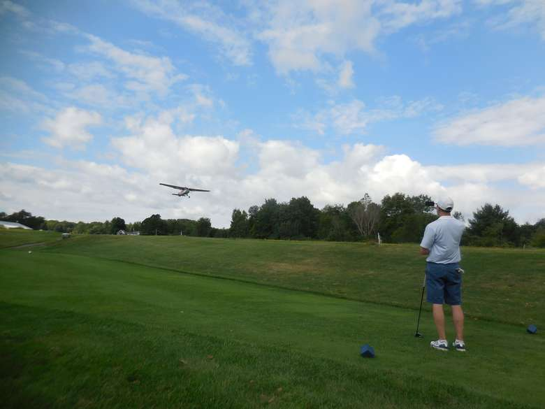 airplane taking off while a golfer looks on