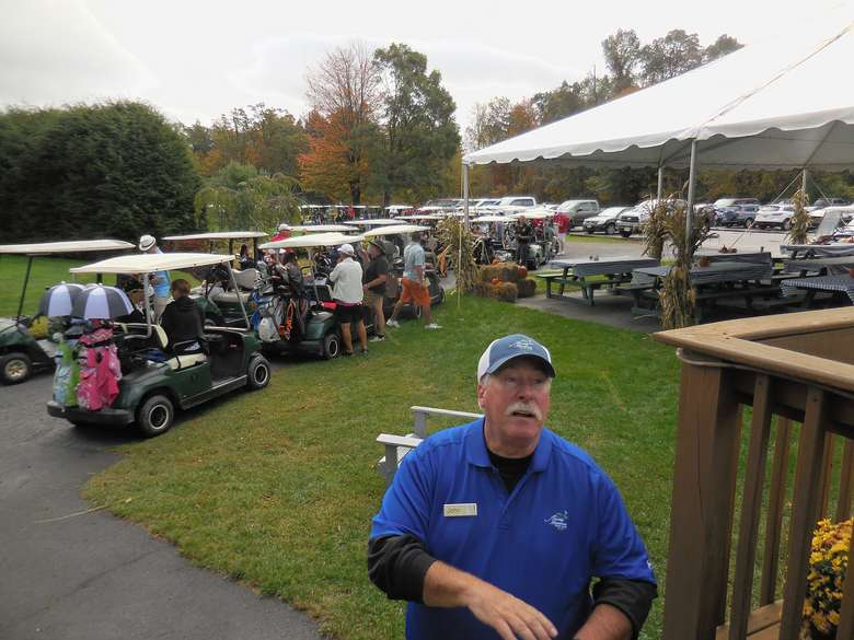 several golf carts loaded with people and gear before a tournament