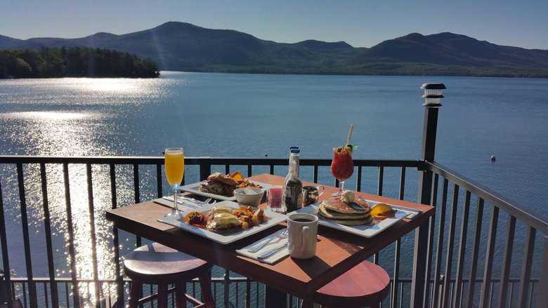 table with brunch food and drinks on a patio overlooking lake george