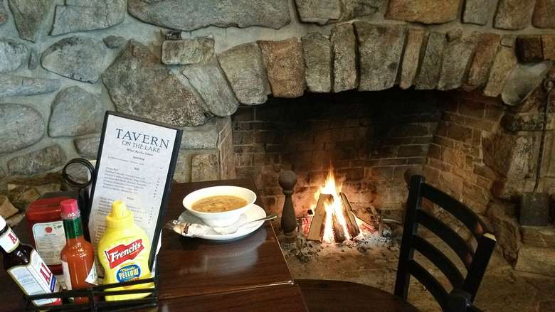 bowl of soup on a table in front of a fireplace