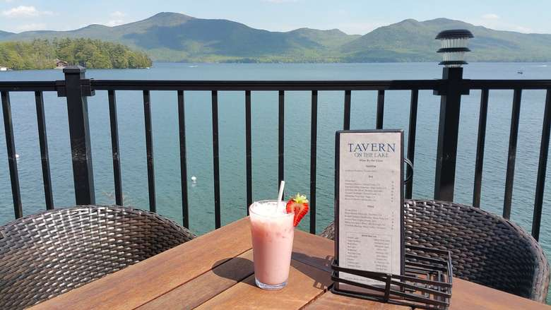 beverage with a strawberry garnish on a patio table overlooking lake george