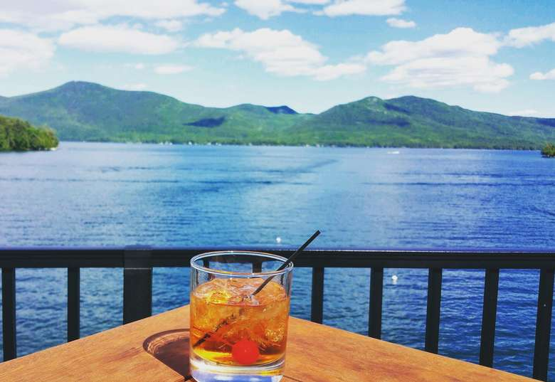 cocktail in a rocks glass on a table overlooking lake george