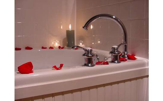 large tub covered in rose petals with a lit candle on the corner of the tub reflecting light from the tub surround
