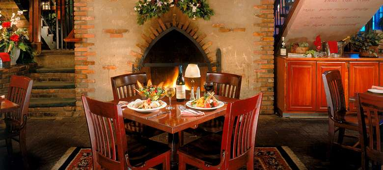 table for four at a restaurant set up in front of a fireplace