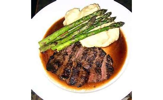 sliced steak on a plate with asparagus, mashed potatoes, and sauce
