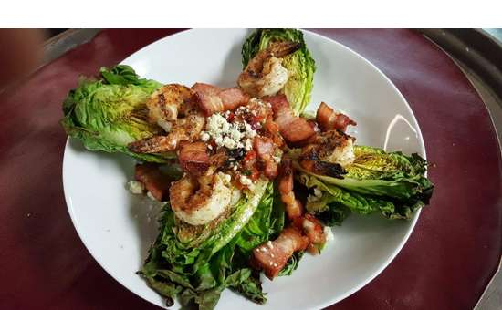 grilled shrimp and bacon on top of large lettuce leaves