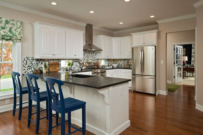 new kitchen with stainless steel appliances, hardwood floors, and three blue barstools pulled up to the counter