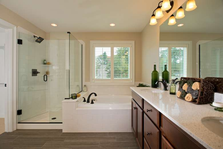 master bathroom with a glass shower, soaker tub, and large vanity
