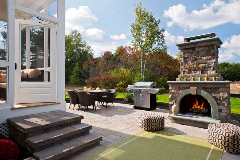 outdoor fireplace, grill, and dining table on a patio