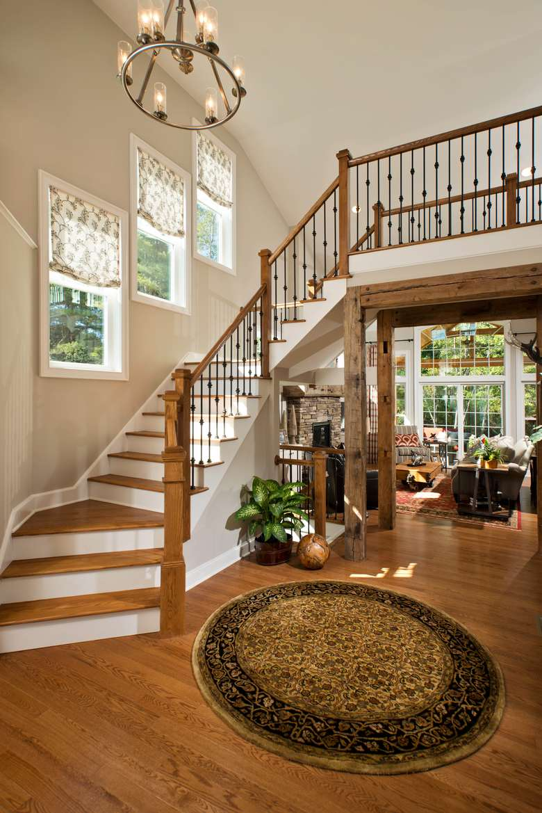 foyer of a new home with a large staircase and a hanging light fixture