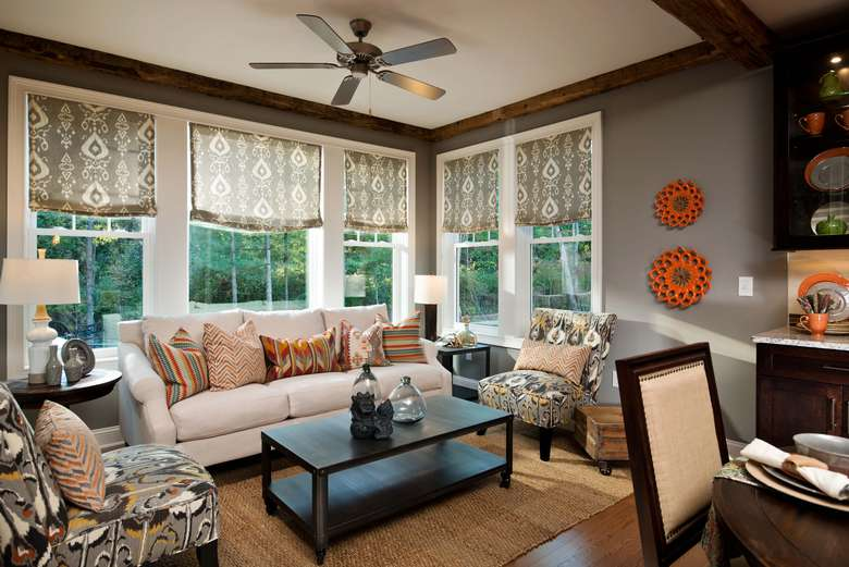 family room in a house with gray walls, a ceiling fan, and comfortable furniture