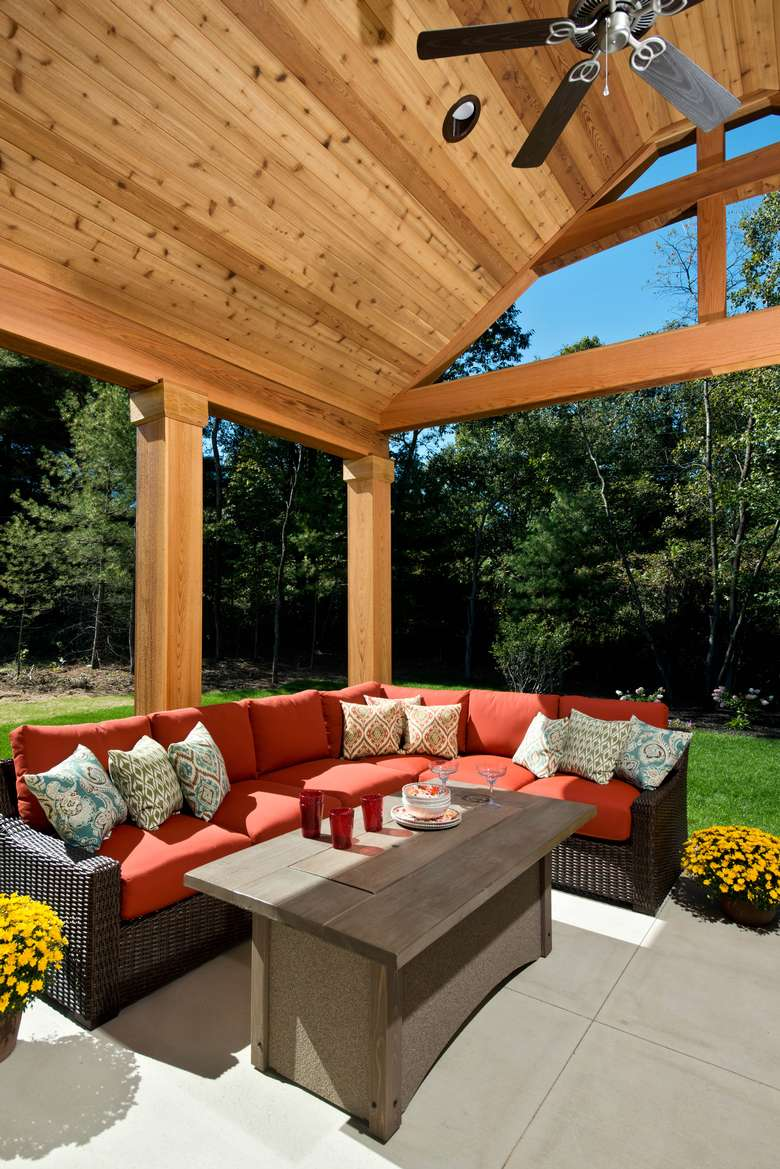 covered porch with a ceiling fan and a large red couch