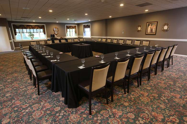 four tables set up in the shape of a square for a conference or meeting