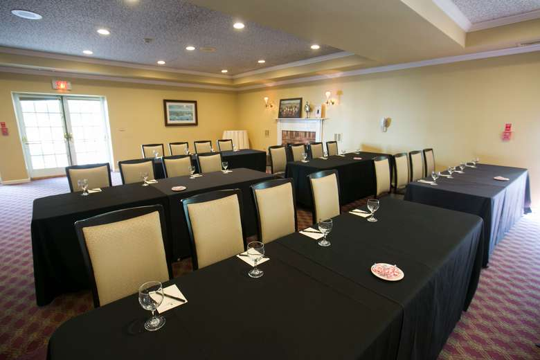 five rectangular tables each set for four people for a meeting or conference