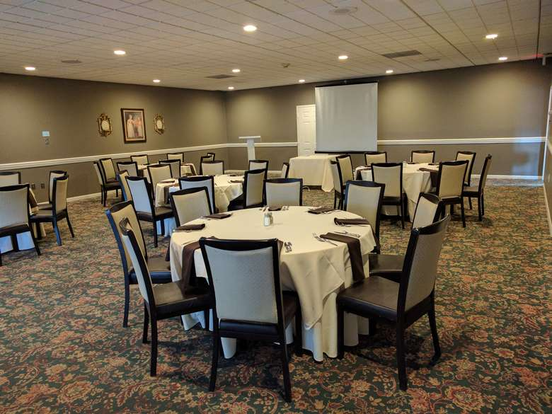 round tables in a banquet hall set up simply with white tablecloths