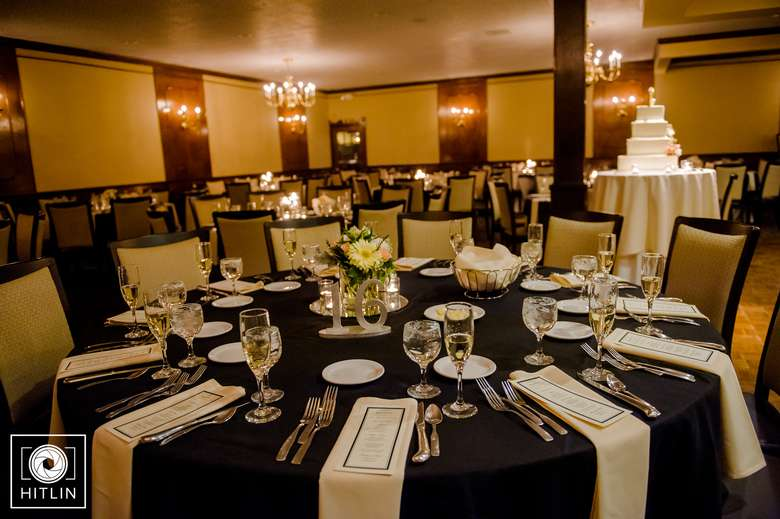 round tables set up for a banquet with black tablecloths, white napkins, and a small menu on top of the napkins